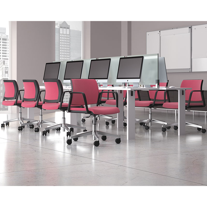 A row of pink swivel chairs in front of a white desk with screens on