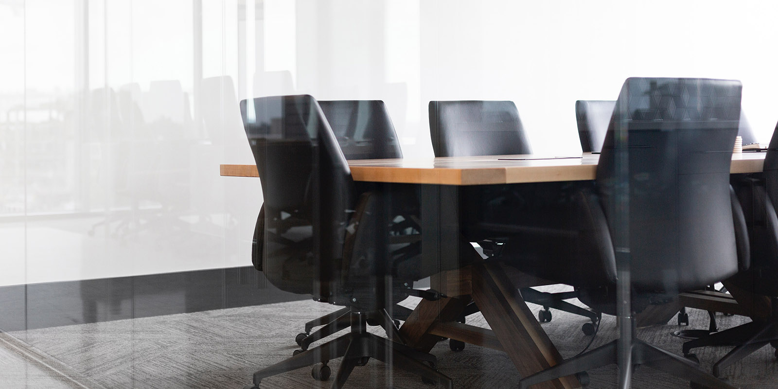 Black chairs around a boardroom table