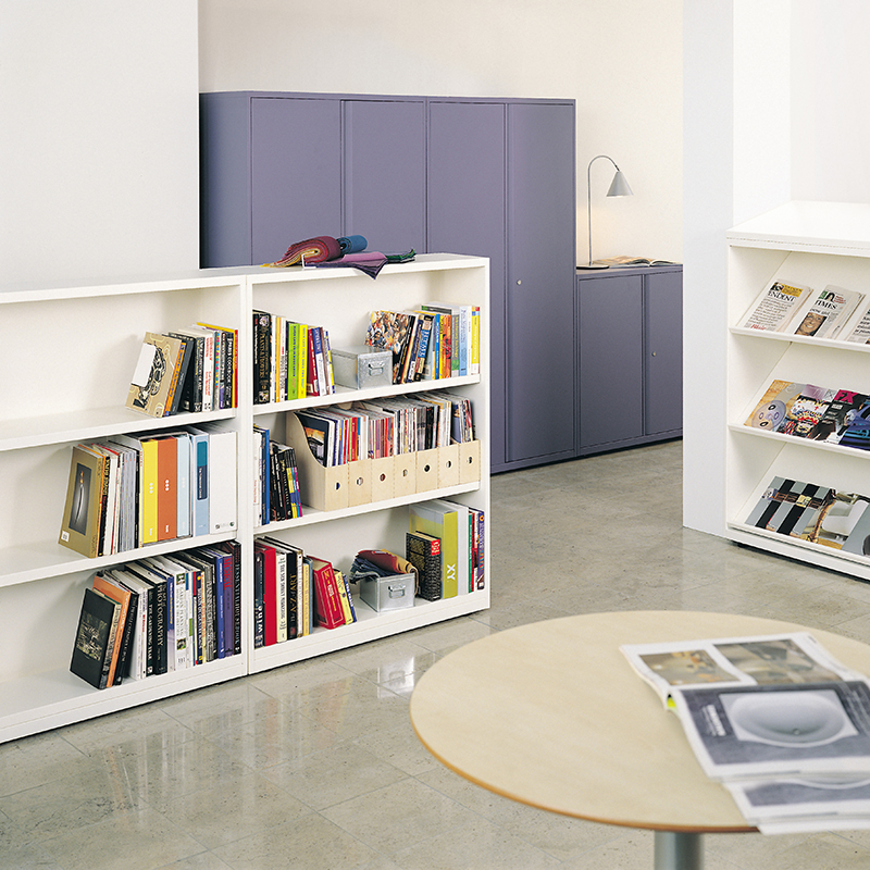White bookcases filled with books, magazines and newspapers, in an office or reception setting with a coffee table and storage cabinets