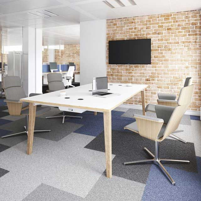 Office setting with chrome and grey chairs around a rectangular white and wooden table